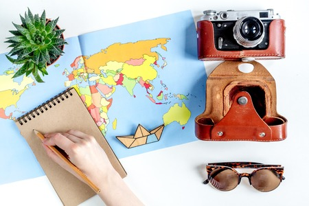 stuff: vacation concept with traveller outfit map and camera on white desk background top view