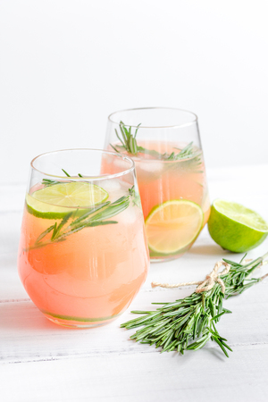 breackfast: sliced lime, rosemary and natural juice in glass on white table background