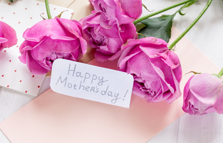 present design with Mothers day text and greeting-card on wooden desk