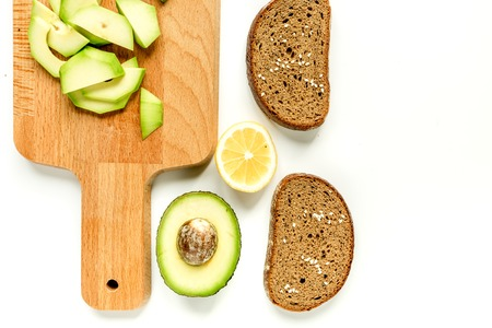 homemade sandwiches with avocado on white table background top view