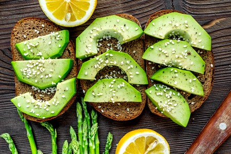 making healthy lunch with bread, lemon, avocado and knife kitchen top view