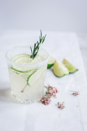breackfast: sweet fresh cocktail with flowers and cut lime on stone desk background Stock Photo