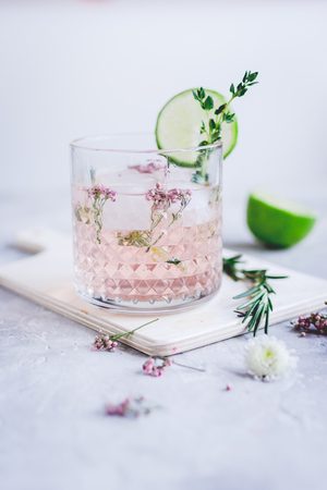 breackfast: natural alcoholic cocktail with herbs and cut lime for summer party on stone desk background