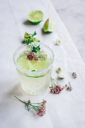 breackfast: summer homemade fresh juice with cut lime and blossom on stone table background