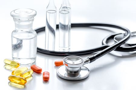 meds and stethoscope on doctors workplace on white table background