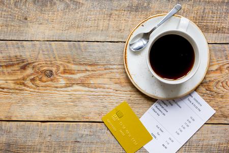 レストランの勘定を払ってクレジット カードや木製のテーブル背景平面図モックアップのコーヒーで