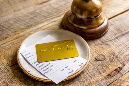 plate and receipt bill for payment by credit card wooden table background