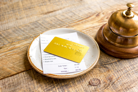 credit card for paying, waiter ring and check on cafe rustic wooden desk background Stock Photo