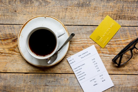 paying: cup of coffee and receipt bill for payment by credit card on wooden table background top view