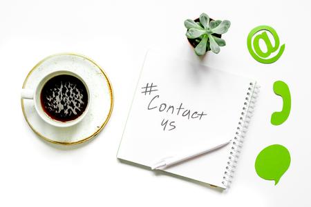 電子メールお問い合わせインターネット アイコンと白の作業デスク背景トップ ビューにコーヒーのコンセプト