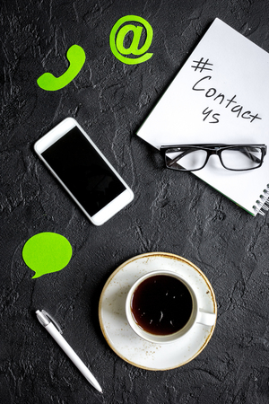 メール印と暗い背景の平面図上でのモバイル クライアント サポート サービス ワークデスクとお問い合わせ 写真素材