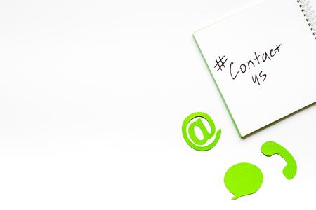 連絡先メールを私たちとクライアント サポート サービス ワークデスク ホワイト バック グラウンド トップ ビュー モックアップの標識します。 写真素材