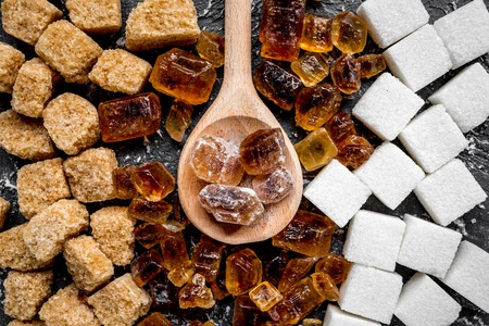 sugar in lumps for sweet food cooking on kitchen dark table background top view pattern