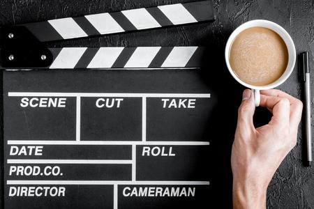 screenwriter: Screenwriter desktop with movie clapper board on dark background top view