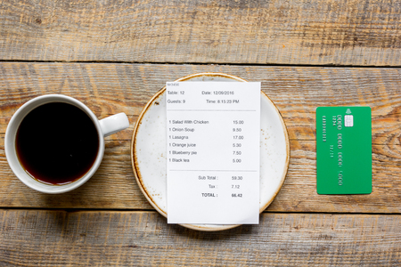 restaurant bill, credit card and coffee on wooden table background top view