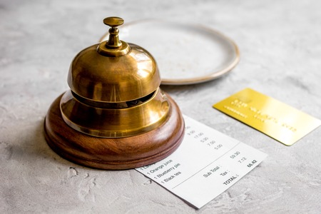 recibo: credit card for paying, waiter ring and check on cafe gray stone desk background Foto de archivo