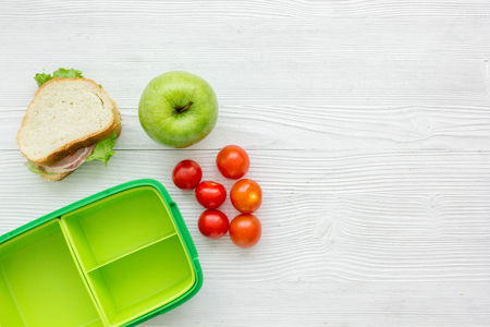 homemade lunch with apple, tomato and sandwich in green lunchbox on wooden table background top view mockup Stock Photo