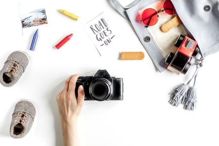 food stuff: tourist equipment with toys and photo camera for traveling with kids on white background top view