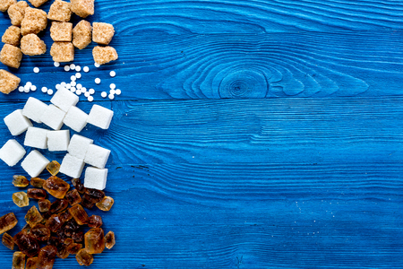 refined: sugar in lumps for sweet food cooking on kitchen blue table background top view mock up