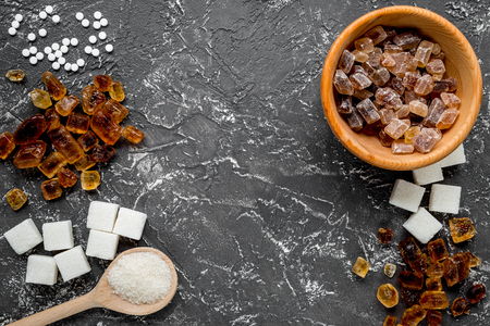 refined: Sugar in lumps for sweet food cooking on kitchen dark table background top view mock up