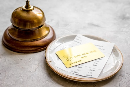 credit card for paying, waiter ring and check on cafe stone desk background Stock Photo