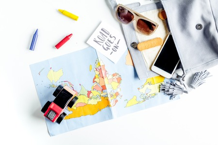 accessories for treveling with children and mobile phone on white table background top view Foto de archivo