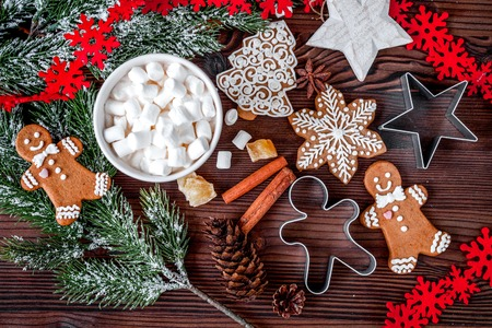 Christmas gingerbread, spruce branches on dark wooden background Banco de Imagens