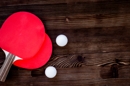 Red racket for   ball on gray wooden background top view