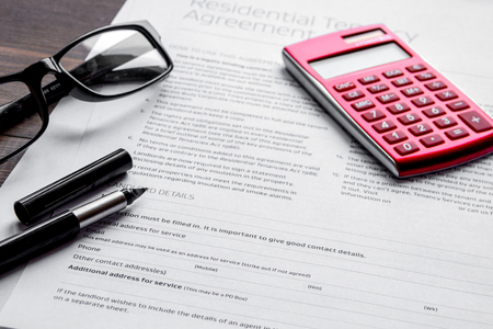 concept of house rental. rental agreement with calculator, pen and spectacle on dark wooden background