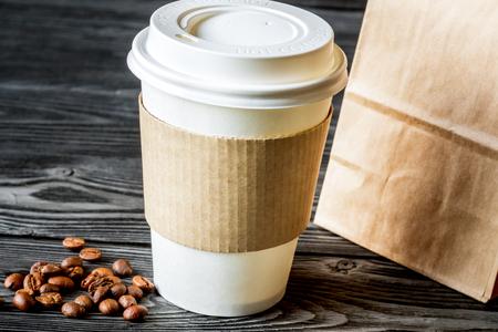 llevar tazas de café, una bolsa de papel y granos de café sobre un fondo de madera.