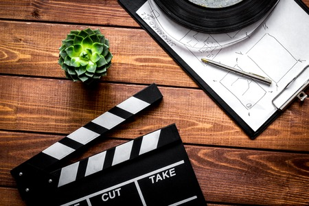 Work screenwriter on wooden background top view