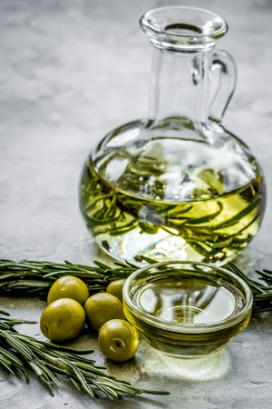 oil in carafe with spices and olive on stone background