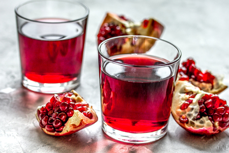 Glass of pomegranate juice with fresh slices on stone