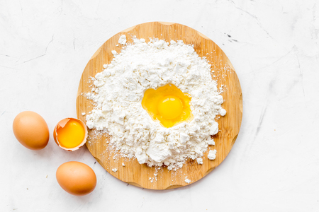 Making dough concept. Pile of flour and eggs on white top view