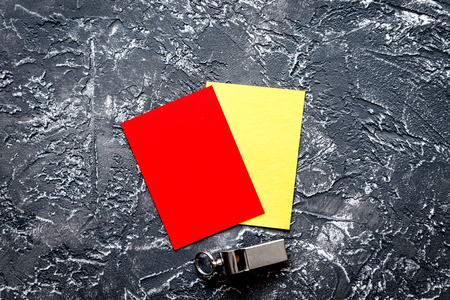 red and yellow cards on dark background top view