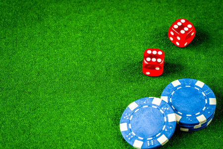poker chips and dice on green background top view