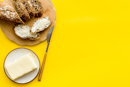 Traditional breakfast. Wholegrain bread on cutting board with butter on plate on yellow background top view