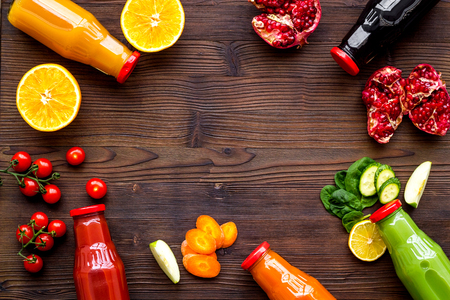 bottles with fresh carrot, tomato, apple, cucumber, lemon, pomegranate juices on wooden background top view copyspace