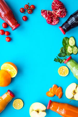 Bottiglie con succhi di carota fresca, pomodoro, mela, cetriolo, limone, melograno su copyspace blu con vista dall'alto Archivio Fotografico