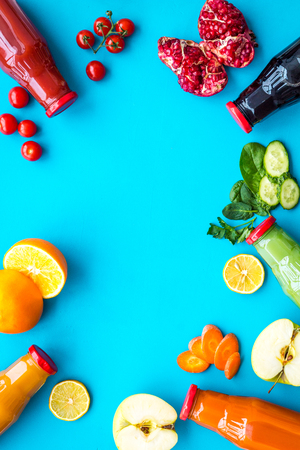 Bottles with fresh carrot, tomato, apple, cucumber, lemon, pomegranate juices on blue top view copyspace Imagens