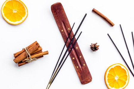air freshener sticks with cinnamon and orange on white background top view