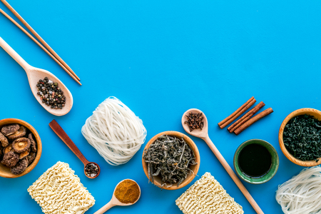 Rice vermicelli, noodles, spices, weeds pattern to cook Chinese and Japanese food on blue background top view copy space