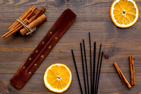 air freshener sticks with cinnamon and orange on wooden background top view Stock Photo