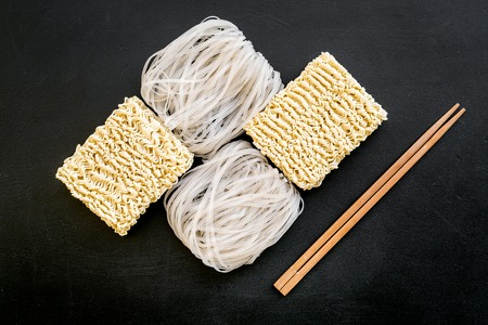 Chinese, Japanese food cooking with rice vermicelli, noodles and sticks on black background top view geometric pattern