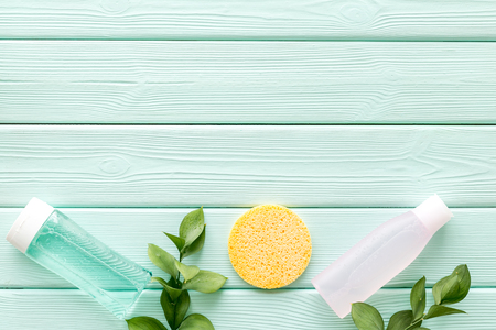 skin care cosmetics with facial tonic, mycelial water and sponge on mint greem background top view mockup