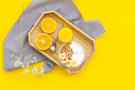 granola with banana slices and orange juice for breakfast on yellow background top view Stock Photo
