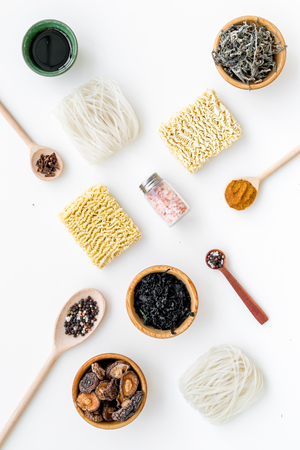Geometric design with Chinese and Japanese products, noodles, weeds, spices, mushrooms white background top view pattern