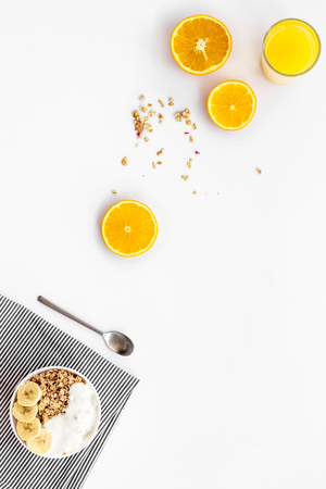 granola with banana slices and orange juice for breakfast on blue background top view copyspace