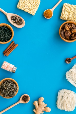 Geometric design with Chinese, Japanese products, noodles, weeds. spices, mushrooms on blue background top view mockup