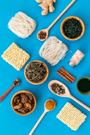 Chinese and Japanese food cooking with ginger, spices and noodles on blue background top view geometric pattern 스톡 콘텐츠